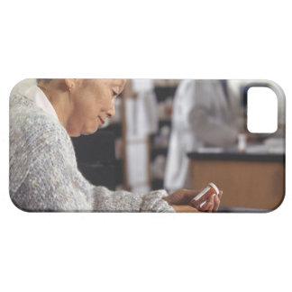 Senior woman in pharmacy reading medicine bottle iPhone 5 cover