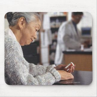 Senior woman in pharmacy reading medicine bottle mouse pad