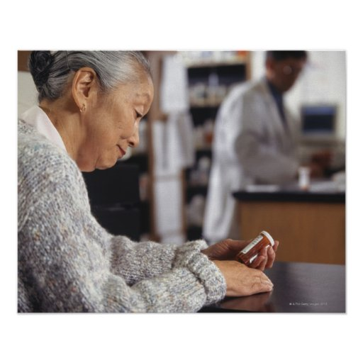 Senior woman in pharmacy reading medicine bottle poster
