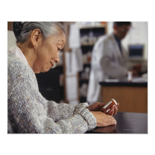 Senior woman in pharmacy reading medicine bottle poster