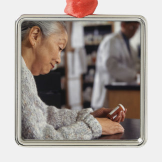 Senior woman in pharmacy reading medicine bottle Silver-Colored square decoration