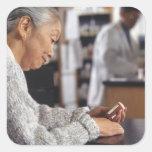 Senior woman in pharmacy reading medicine bottle square sticker
