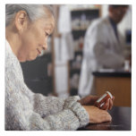 Senior woman in pharmacy reading medicine bottle tile
