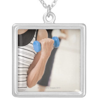 Seniors exercising with dumbbells in a health square pendant necklace