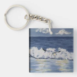 serene seabird chasing waves on a keychain