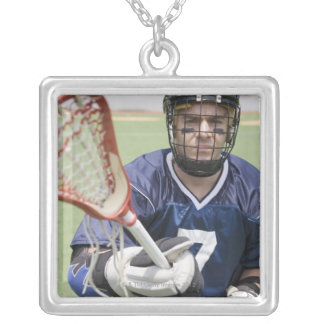 Serious lacrosse player holding crosse square pendant necklace