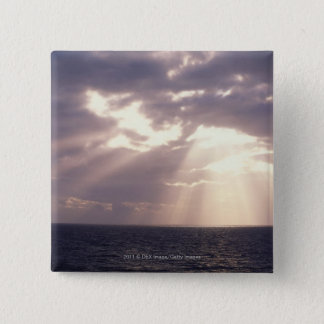 Setting sun shining through clouds over ocean 15 cm square badge