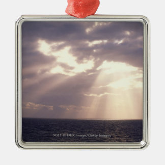 Setting sun shining through clouds over ocean christmas ornament