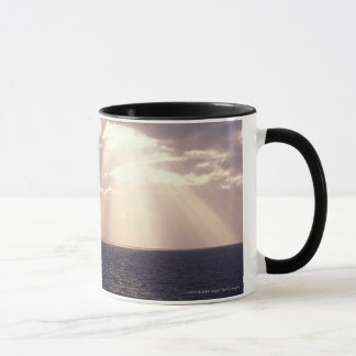 Setting sun shining through clouds over ocean mug