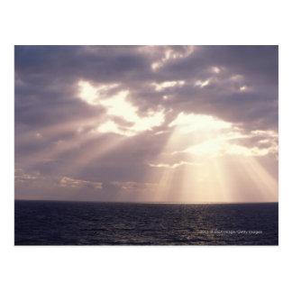 Setting sun shining through clouds over ocean postcard