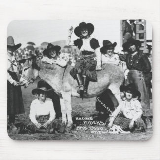 Seven rodeo cowgirls jokingly posing with a donkey mouse pads