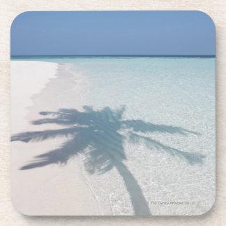 Shadow of a palm tree on a deserted island beach coaster