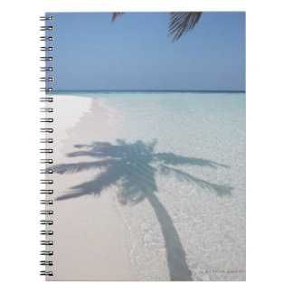 Shadow of a palm tree on a deserted island beach notebook