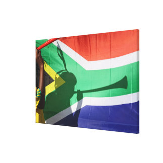 Shadow of soccer supporter blowing vuvuzela, canvas print