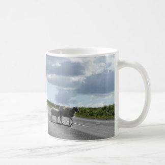 Sheep on road coffee mug