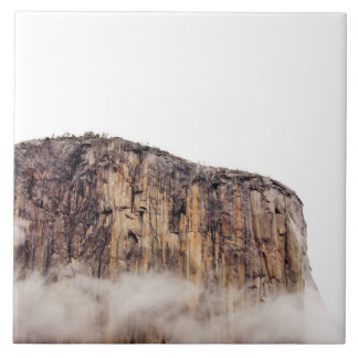 Sheer cliff rising above clouds tile