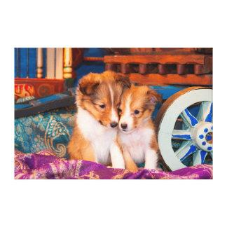 Shetland Sheepdog puppies sitting by wooden wagon Canvas Print