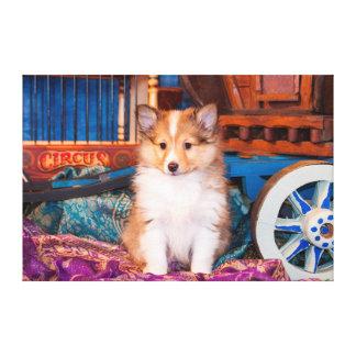 Shetland Sheepdog puppy sitting by small wagon Canvas Print