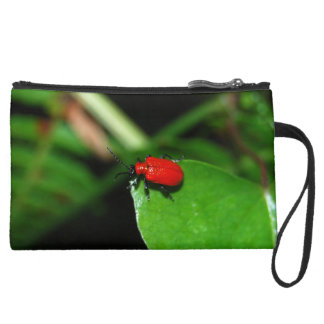 Shining red beetle in the green leaf wristlet purses