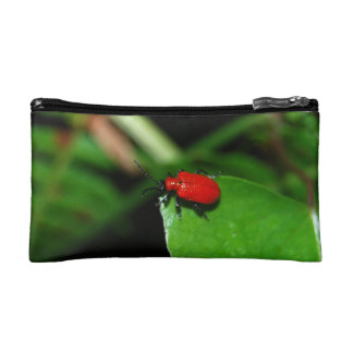 Shining red beetle in the green leaf cosmetics bags