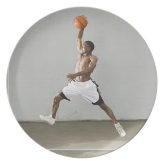 shirtless man jumping with a basketball plate