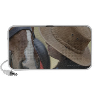 Side profile of a teenage girl touching a horse iPhone speaker