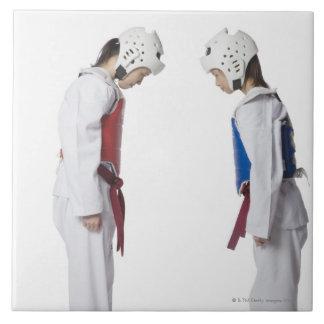 Side profile of two taekwondo players bowing large square tile