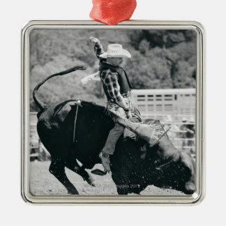 Side view of rider hanging on to bucking bull christmas ornament