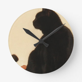 Side View Silhouette of A Black Cat Sitting On A R Round Clock