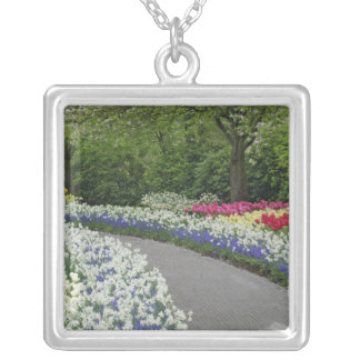 Sidewalk pathway through tulips and daffodils, square pendant necklace