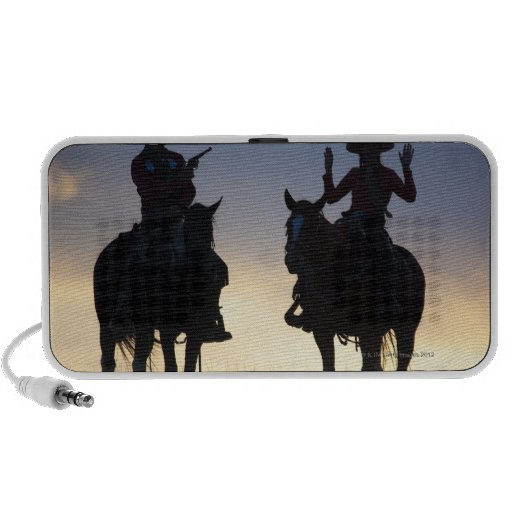 Silhouette of a Cowboy targeting his pistol to a Portable Speaker