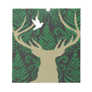 Silhouette of a deer, a dove and a star against a notepad