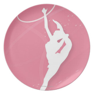 Silhouette of a female gymnast performing with a plate