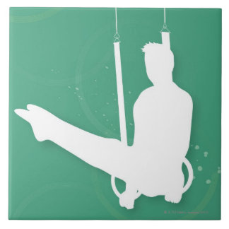 Silhouette of a man performing gymnastics tile