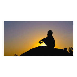 Silhouette of boy sitting o rock photo cards