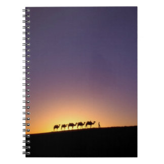 Silhouette of camel caravan on the desert at notebook