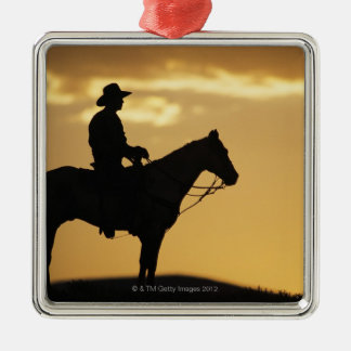 Silhouette of cowboy on horseback at sunset or christmas ornament