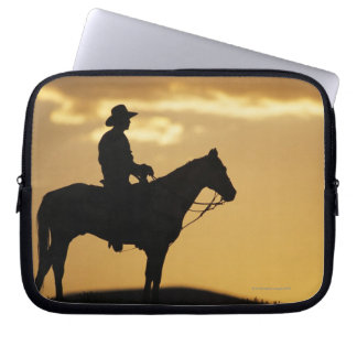 Silhouette of cowboy on horseback at sunset or laptop sleeve