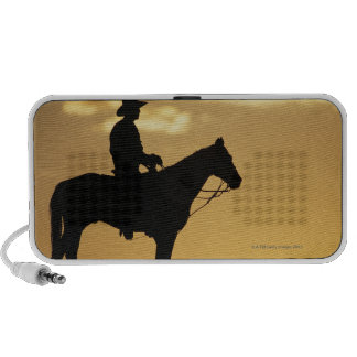Silhouette of cowboy on horseback at sunset or speakers