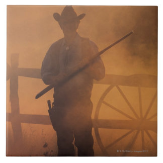 Silhouette of cowboy with rifle in hand tile