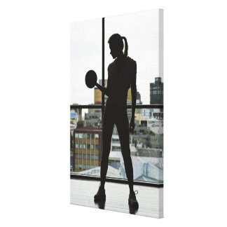 Silhouette of woman lifting weights at gym canvas print