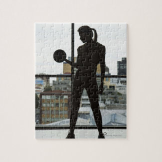 Silhouette of woman lifting weights at gym puzzle