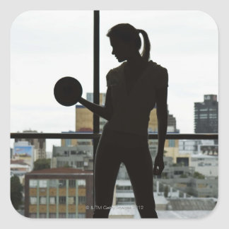 Silhouette of woman lifting weights at gym square sticker