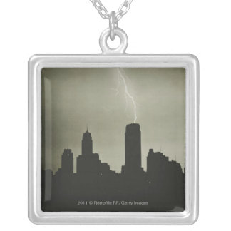 Silhouettes of skyscrapers and lightning in sky silver plated necklace