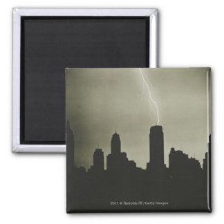 Silhouettes of skyscrapers and lightning in sky square magnet