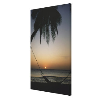 Silhuetted empty hammock at sunset canvas print