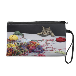 Silver tabby cat climbing over edge of table wristlet purse