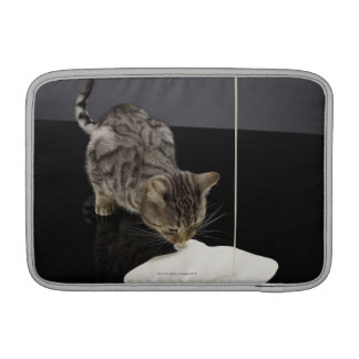 Silver tabby cat drinking cream from floor sleeves for MacBook air