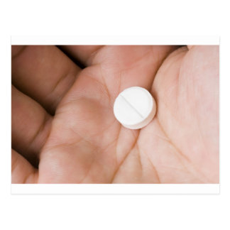 Single white pill in palm postcards