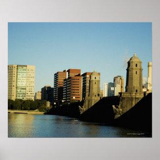 Skyscrapers near a bridge across a river, poster